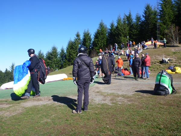 Paragliders preparing to jump from Poo Poo Point as hikers look on